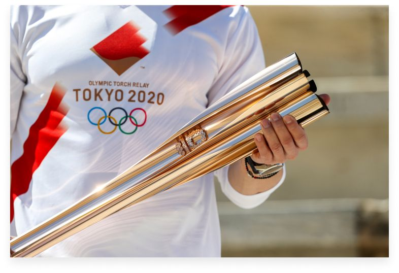 man in tokyo olympics 2020 shirt holding torch
